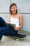 Young girl siting on skateboard in the cty with tablet. Stock Image