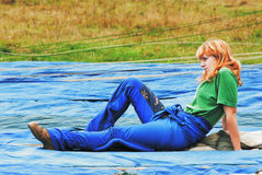 The young girl sits on the airdrome. Young sportswomen of parashute  competition Stock Photography