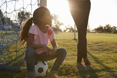 Young girl sits on ball next to her mum on a football pitch Royalty Free Stock Image