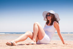 Young girl sits on the beach Stock Photos