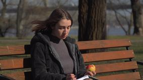 Young girl sits on bench in park, eats apple and writing in notebook. Young girl sits on bench in park and writes in her notebook. Pretty female is relaxing stock video