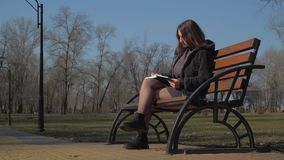 Young girl sits on bench in park and writes in her notebook. Pretty female is relaxing alone on the nature. Prores codec. Camera in motion stock footage