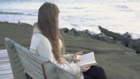 A young girl sits on a bench by the sea reads a book at sunset of the evening day. 4K. A child reading on the beach at stock video footage