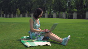 A young girl sits on blanket and typing on a laptop outdoors stock video