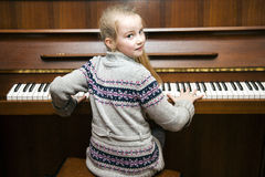 Young girl sits at brown  upright piano Royalty Free Stock Image