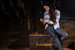 Young girl sits on a chest and considering the lock to get out o. F the trap, escape the room game concept stock photography