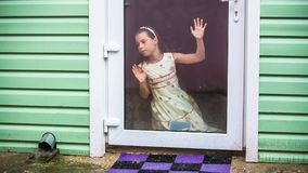 Girl looks at the rain. A young girl sits in front of a glass door and looks at the rain