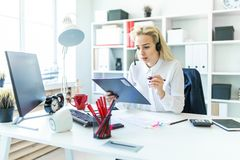 A young girl sits in headphones with a microphone at the desk in the office and makes notes in the document. A slender young girl in a white blouse is working Stock Photography