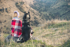 A young girl sits with her friend the husky dog on the edge of the gorge at sunset Royalty Free Stock Photo