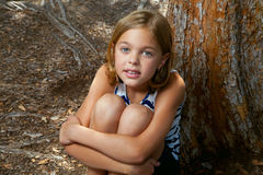 Young Girl Sits While Hugging Legs. A young girl sits by a tree, hugging her legs, as she looks up at the camera. She has a slightly confused look, almost a Stock Images