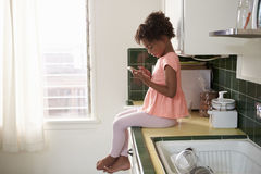 Young Girl Sits In Kitchen And Plays With Mobile Phone Stock Photos