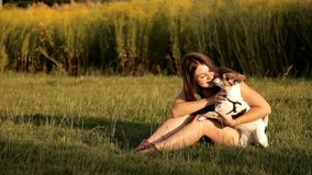 Young girl sits on a lawn in the park and kisses her dog