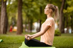 Young girl sits in the lotus position with closing eyes doing exercises with other girls on green grass in the park on a stock photos