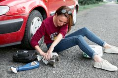 A young girl sits near a broken car and makes repairs to the electric generator, next to her there are bad parts, tools and first. A young girl sitting near a stock photography