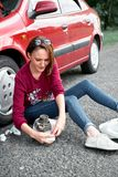 A young girl sits near a broken car and makes repairs to the electric generator, next to her there are bad parts, tools and first. A young girl sitting near a royalty free stock image