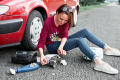 A young girl sits near a broken car and makes repairs to the electric generator, next to her there are bad parts, tools and first. A young girl sitting near a stock images
