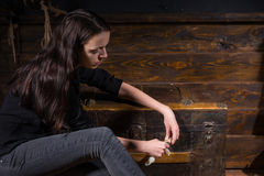 Young girl sits near a chest and trying to solve a conundrum to. Get out of the trap, escape the room game concept Stock Image