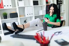 A young girl sits in the office, threw her legs on the table and holds the phone in her hands. A young girl sits in the office, threw her legs on the table and royalty free stock photo