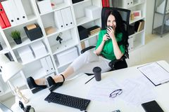 A young girl sits in the office, threw her legs on the table and holds the phone in her hands. A young girl sits in the office, threw her legs on the table and royalty free stock image