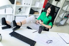 A young girl sits in the office, threw her legs on the table and holds the phone in her hands. A young girl sits in the office, threw her legs on the table and stock photography