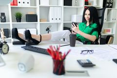 A young girl sits in the office, threw her legs on the table and holds the phone in her hands. A young girl sits in the office, threw her legs on the table and royalty free stock photos