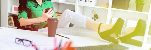 A young girl sits in the office, threw her legs on the table and holds the phone in her hands. A young girl sits in the office, threw her legs on the table and stock images