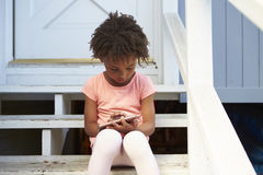 Young Girl Sits On Outdoor Steps Playing With Mobile Phone Stock Photos