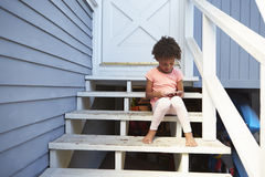 Young Girl Sits On Outdoor Steps Playing With Mobile Phone Royalty Free Stock Photo