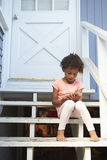 Young Girl Sits On Outdoor Steps Playing With Mobile Phone Royalty Free Stock Photography