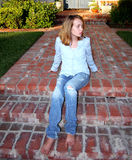 Young Girl Sits On Porch. Pretty barefoot preteen sits waiting, watching from her home porch steps Stock Photos