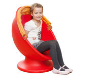 A young girl sits in a red chair Stock Photo