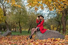 Young girl sits on a rock in an autumn park in a red coat and black hat on her head Stock Photography
