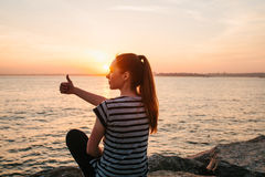 A young girl sits on the rocks next to the sea at sunset and shows a hand sign which means cool. Rest, vacation. A young girl sits on the rocks next to the sea Stock Photography