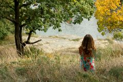 A young girl sits and stares at the water Stock Photos