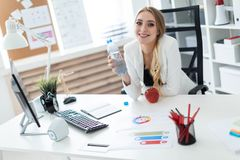A young girl sits at a table in the office and holds a bottle of water in her hand. Before the girl on the table is an stock image