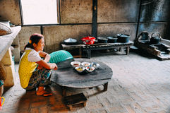 A young girl sits in a traditional kitchen in a small village in Bagan. A young girl sits in a traditional kitchen in a small village in Bagan, Myanmar Stock Image