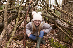 Young girl sits under shelter of tree branches, full length Stock Photography