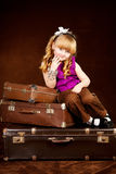 Young girl sits on vintage baggage Royalty Free Stock Photography