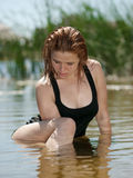 Young girl sits in the water. Young girl sits and looks down in the water in summer river Stock Photos