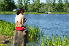 Young girl sits at water and fishes Stock Photo