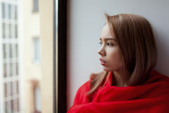 A young girl sits by the window, wrapped in a red blanket and thinks.  Stock Photography