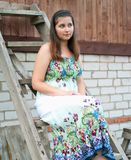 Young girl sits on a wooden ladder Royalty Free Stock Photos