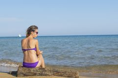 Young girl sitting alone at the beach Royalty Free Stock Images
