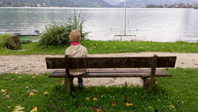 Young girl sitting alone on a bench. Staring into the wilderness of placid lake. This picture is in colour Royalty Free Stock Image