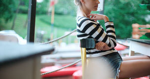 Young girl sitting alone at outdoors cafe. Pretty young caucasian girl sitting at outdoors cafe and waiting for someone Stock Photos