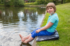 Young girl sitting with bare feet in pond. Young blonde caucasian girl sitting on green grass with bare feet in water of pond Stock Photos