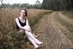 Young girl sitting barefoot on the ground road near wheaten field, concept of summer and travel royalty free stock images