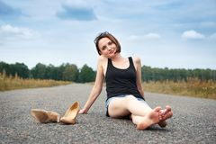Young girl sitting barefoot on the road, she left her shoes on the road and forgot them, the concept of summer and travel stock photos