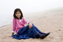 Young girl sitting on beach Stock Image