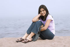 Young girl sitting on beach Stock Photo